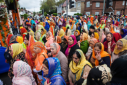 Slough, UK. 28th April 2019. Sikhs pay their respects to the Sacred Sri Guru Granth Sahib Ji during the Vaisakhi Nagar Kirtan procession from the Gurdwara Sri Guru Singh Sabha to the Ramgarhia Sikh Gurdwara. Vaisakhi is the holiest day in the Sikh calendar, a harvest festival marking the creation of the community of initiated Sikhs known as the Khalsa.
