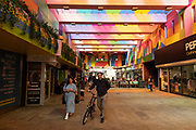 People out shopping under the colourful new roof over Hertford Street in the UK City of Culture 2021 on 23rd June 2021 in Coventry, United Kingdom. The UK City of Culture is a designation given to a city in the United Kingdom for a period of one year. The aim of the initiative, which is administered by the Department for Digital, Culture, Media and Sport. Coventry is a city which is under a large scale and current regeneration.