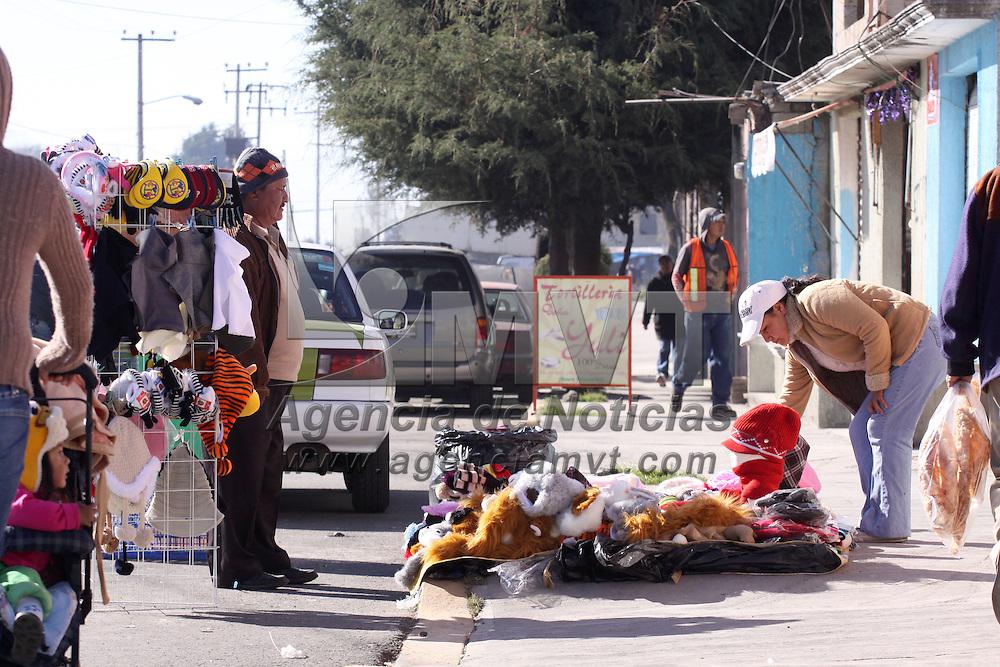 TOLUCA, México.- Algunos padres de familia comienzan a hacer compras contra el frío, guantes, bufandas, gorros son algunas de las prendas que ofrecen vendedores ambulantes. Agencia MVT / José Hernández. (DIGITAL)