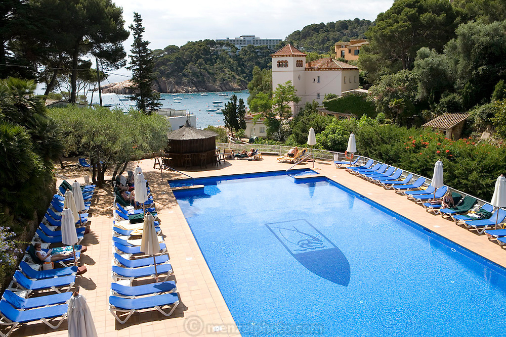 The pool at the Hotel Aigua Blava, Costa Brava, Spain. In the distance, across the bay on a bluff is the white Parador de Aigua Blava.