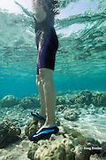 visitor standing on coral at Kahalu'u Beach, Kahaluu Beach Park, Keauhou, Kona, Hawaii Island ( the Big Island ), Hawaii, USA ( Central Pacific Ocean )
