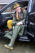 © Licensed to London News Pictures. 11/02/2014. Shepperton and Chertsey, UK. NIGEL FARAGE, leader of UKIP puts on waders before he walks along Chertsey Bridge Road. Flooding in SHEPPERTON AND CHERTSEY in Surrey today 11th February 2014 after the River Thames burst its banks. The Environment Agency has issued 14 Severe Flood Warnings alone the Thames. Photo credit : Stephen Simpson/LNP