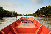 Apr. 3, 2010 - KHUN SAMUTCHINE, THAILAND:  A boat cuts through the canals and mangroves near Khun Samutchine. Rising sea levels brought about by global climate change threaten the future of Khun Samutchine, a tiny fishing village about 90 minutes from Bangkok on the Gulf of Siam. The coastline advances inland here by about 20 metres (65 feet) per year causing families to move and threatening the viability of the village. The only structure in the village that hasn't moved, their Buddhist temple, is completely surrounded by water and more than 2 kilometers from the village. The temple and the village have asked the Thai government and several NGOs for help, but the only help so far is a narrow concrete causeway the government is building that will allow people to walk into the temple from a boat landing two miles away. The walk to the village from a closer boat landing is shorter, but over an unimproved mud flat that is nearly impassible in the rainy season.  PHOTO BY JACK KURTZ