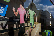 Detail of an illustration of two joggers wearing Karrimor sportswear, running in the window of a shop in central London.