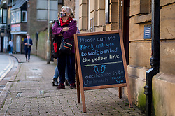 © Licensed to London News Pictures. 15/12/2020. RICKMANSWORTH, UK. A social distancing sign and a queue outside a bank in Rickmansworth, Hertfordshire.  The historic town will be elevated to Tier 3 Covid Alert Level tomorrow, as part of the Three Rivers District Council area joining London and other areas of the South East as the number of coronavirus cases continues to rise.  Photo credit: Stephen Chung/LNP