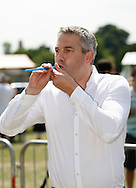 Photo by Andrew Tobin/Tobinators Ltd - 07710 761829 - Steve Barclay MP (Con N E Cambs) takes aim during the World Peashooting Championships held at Witcham, Cambridgeshire, UK on 13th July 2013. Run in conjunction with the village fair, the Championships have been held in Witcham since 1971 when they were started by a Mr Tyson, the village schoolmaster, in order to raise funds for the village hall.Competitors come from as far afield as the USA and New Zealand to attempt to win the event. The latest technology is often used, including laser sights and titanium and carbon fibre peashooters. All peashooters must conform to strict length rules, not exceeding 12 inches, and have to hit a target 12 feet away. Shooting 5 peas at a plasticine target attached to a hay bale, the highest scorers move through the initial rounds to a knockout competition, followed by a sudden death 10-pea shootout.