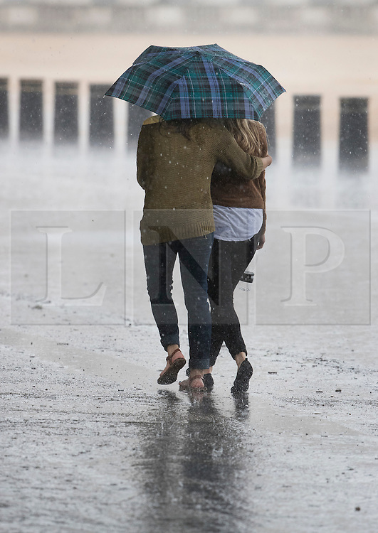 © Licensed to London News Pictures. 12/07/2016. London, UK. A couple get a soaking as a sudden rain storm hits central London. Photo credit: Peter Macdiarmid/LNP