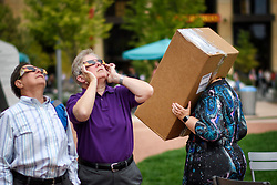August 21, 2017 - Minneapolis, Minnesota, USA - Margaret Anderson Kelliher, right watched the eclipse with the help of a box with a pinhole at 1:03 p.m.  Kelliher, head of the Minnesota High Tech Association and some of her co co workers made the pinhole viewers this morning.  Margaret Molinari and Ann Seha watched through shaded solar eclipse glasses from the Commons Park.      ] GLEN STUBBE • glen.stubbe@startribune.com Monday August 21, 2017 (Credit Image: © Glen Stubbe/Minneapolis Star Tribune via ZUMA Wire)