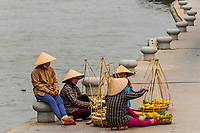 Street vendors taking a break along the Thu Bon River, Hoi An, Vietnam.