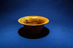 Hand turned wooden oak bowl on dark blue background