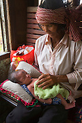 Newborn baby with her grandmother on a train. The baby undergoes a traditional Kruu medicine treatment. A concoction of powders are placed on her 'middle eye' and a place where it is considered to be the soft part of the babies skull, to harden it. ..Touth Koeun, an ex-Khmer Rouge child soldier turned midwife and trainer, is on the frontline again, but this time campaigning on maternity issues, in Preah Vihear province, Cambodia. The country experiences an extraordinarily high incidence of infant and maternal mortality. The Preah Vihear province, in Cambodia's north, bordering on the Thai border, can be described as an outback rural area, villages often many hours away from a health centre or clinic, and sometimes near the frontline where soldiers and their families are living. Here, Touth Kouen, a locally much respected pioneer and experienced in maternity issues, trains indigenous women, known as 'Traditional Birth Attendants' (TBA's), correct procedures to assist midwives and nurses, to give direct support to mothers and their babies, during ante and post natal periods. Traditional bush medicine and spiritual practices by 'Kruu' bush doctors, involving the killing of endangered species, gathering herbs and plants, whose burnt remains are often ground up into unhealthy potions, and fed to mothers as miracle cures, and postpartum heating, can cause illness and death. The Kruu, and local people in general need to be re-educated, so as to create a healthy nurturing environment for mothers and their babies. Preah Vihear Province, Cambodia