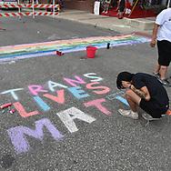 ISAAC GARCIA, San Antonio,  uses street chalk to write Trans Lives Matter on the pavement prior to a Gay Pride celebration in San Antonio Saturday..
