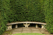 A stone bench supported by sculpted stone figures set in a Yew hedge at Newby Hall, Ripon, North Yorkshire, UK