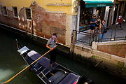Hot gondolier wipes his brow during a heatwave, to the amusement of tourists, in Venice, Italy. The first mention ever of an Italian gondola was in Venice in 1094 and, of course, there have been gondoliers as long as there have been gondolas - so it's one of the oldest professions in the world. Until August 2010, there had never been a single woman gondolier in Venice as licences were always passed down to male family members. Current prices (2015) is 80 Euros for a 40-minute journey (earning them approx 130,000 Euros a year) along the waterways of this old city but rarely do gondoliers wear their straw hat.