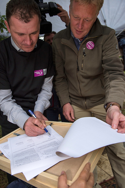 Armenis mayor Petru Vela and Frans Schepers from Rewilding Europe signing the contract about letting the bison out into their area, on the village old grazing grounds, Release of European bison, Bison bonasus, in the Tarcu mountains nature reserve, Natura 2000 area, Southern Carpathians, Romania. The release was actioned by Rewilding Europe and WWF Romania in May 2014.