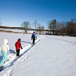 A woman and her son and daughter snowshoe through a snowy field at the Urban Forestry Center in Portsmouth, New Hampshire.