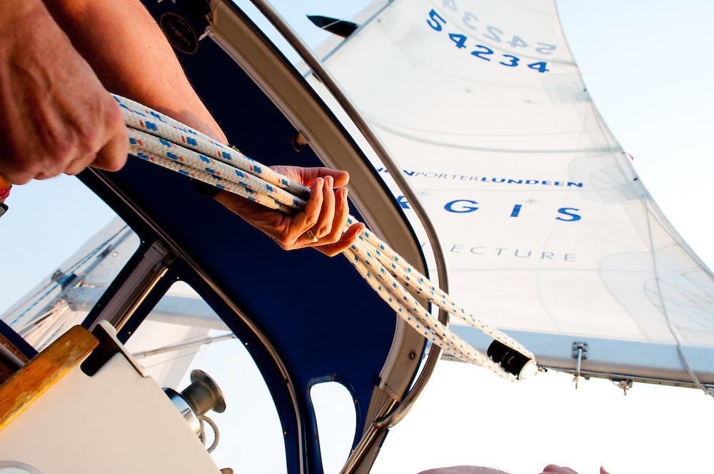 Managing the boom on a sailboat on Elliot Bay during a sailing race, Seattle, Washington.