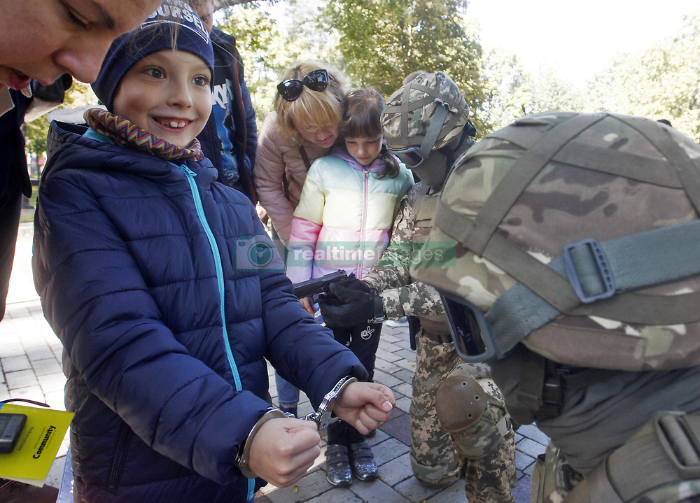 """October 6, 2018 - Kiev, Ukraine - A child stands with handcuffs on his hands during a ''City of professions'' children's  festival in Kiev, Ukraine, on 6 October 2018. The """"City of Professions"""" is a children's career-oriented festival whose goal is to provide children with the opportunity to try themselves in different professions - rescuers, firemen, canine experts, bomb experts, policemen, doctors, social workers, bankers, criminologists, builders and others. (Credit Image: © Serg Glovny/ZUMA Wire)"""