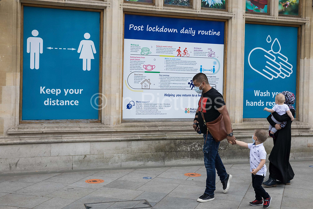 Members of the public wearing face coverings walk past COVID-19 public information displays on 21st August 2020 in Slough, United Kingdom. Slough has been listed by Public Health England PHE and the Department for Health and Social Care DHSC as an 'area of concern' for COVID-19 following a rise in positive coronavirus cases over the last two weeks.