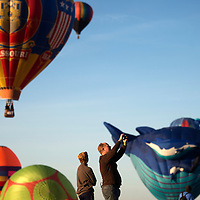 Nick Lucas, right, and his son Kyle photograph and watch as hundred of balloons take off in the Farewell Ascension of the Albuquerque International Balloon Fiesta Sunday.
