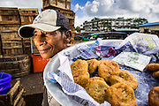 13 JUNE 2013 - YANGON, MYANMAR:  A fried snack vendor waits for customers in the Annawa Fish Market. The Annawa Fish Market in Yangon is one of the largest fish markets in Myanmar. It serves as both a wholesale and retail market and serves both exporters and domestic customers. With thousands of miles of riverine waterways and ocean coastline Myanmar has a large seafood and fishing industry.   PHOTO BY JACK KURTZ