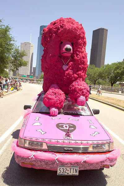 Stock photo of a pink car with a giant pink poodle