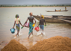© Licensed to London News Pictures. 05/07/2013. Koulikoro,  Mali.  From left to right - Mamouna (12), Balas (13) and Fatumata (11) will spend 8 hours a day dredging sand which has been dropped by the workers. The sand is transported to the shore which is then delivered across Mali for use within the construction industry.   Photo credit: Alison Baskerville/LNP