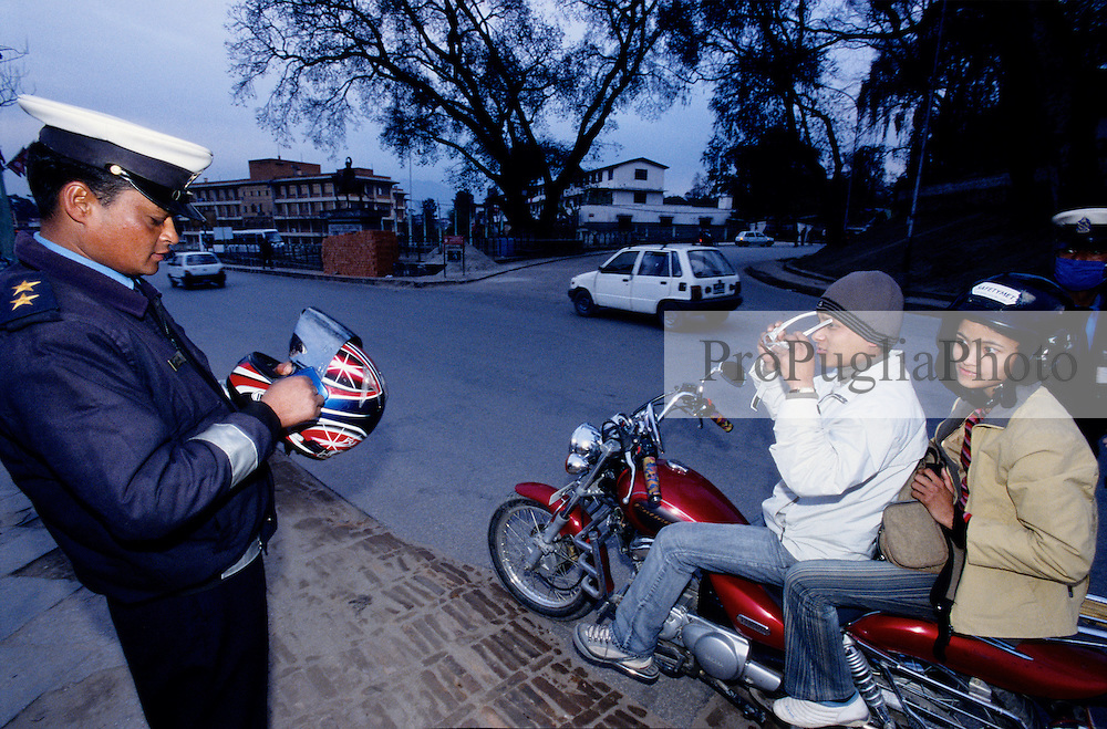 Kathmandu, 17 February 2005. After the King's takeover on the 1st of February 05, traffic Policemen are taking off the wind visors from motorcyclists' helmet due to security reasons.