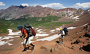 """A pair of hikers trek along the West Maroon Pass trail in Crested Butte, Co. Aspen and Crested Butte are hours apart by car and probably worlds apart in attitude but only separated by 24 miles on a map. Many hikers are starting to take one of a number of mountain passes on foot and stay the night in the other town and then hike, bike, drive or fly back the following day. Depending on the route chosen and the ability of the hiker, it takes about 5 to 9 hours to hike between the two towns. Most hikers choose the trails that converge on 12,490-foot West Maroon Pass ? the shortest of the available options at 10.5 miles. The trail offers a steady uphill from either side, with ample time to prepare for the last steep and loose rocky sections before the pass.The historic Town of Crested Butte is a Home Rule Municipality located in Gunnison County, Colorado, United States. A former coal mining town now called """"the last great Colorado ski town"""", Crested Butte is a destination for skiing, mountain biking, and a variety of other outdoor activities.The Colorado General Assembly has designated Crested Butte the wildflower capital of Colorado..(Photo by MARC PISCOTTY / © 2006)"""