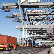 Nederland Zuid-Holland Rotterdam  27-08-2009 20090827 Foto: David Rozing .Serie over logistieke sector.ECT Delta terminal in de haven van Rotterdam. Robotgestuurde wagens vervoeren de containers op de terminal. Onbemande wagens in de rij bij de hijskranen, deze tillen de containers op het zeeschip. .ECT,European Container Terminals, at the Port of Rotterdam. Europe's biggest and most advanced container terminal operator, handling close to three- quarters of all containers passing through the Port of Rotterdam. ECT is a member of the Hutchison Port Holdings group (HPH), the world biggest container stevedore with terminals on every Continent. At the ECT Delta Terminal unmanned, automated guided vehicles  so called AGVs  transport the containers between ship and stack. In the stack, unmanned automated stacking cranes ( ASCs ) ensure that the containers are always stacked in the correct place. Terminal operations are highly automated for discharging and loading large volumes , wagons, wereldhandel, werk, werkzaamheden, zeehaven, zeehavens..Holland, The Netherlands, dutch, Pays Bas, Europe .Foto: David Rozing