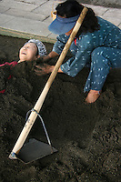 Japanese woman being buried in sand bath at Beppu, one of the few places in Japan where sand is used for spa treatments. Beppu's sand bath is on Shoningahama Beach, and bathers will need to take a bath before roasting in sand, then another bath afterwards to get off the sand.