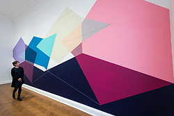 """© Licensed to London News Pictures. 29/10/2020. LONDON, UK. A staff member views a wall painting called """"Happy Overture"""", 1984, by Lydia Okumura. Preview of """"Female Minimal:  Abstraction in the Expanded Field"""", an exhibition of geometric abstract art at Galerie Thaddeus Ropac in Mayfair.  On display are works by 13 female artists from 10 countries many of whom were previously written out of art history due to their gender or politics at the time.  The show suns 29 October to 18 December.  Photo credit: Stephen Chung/LNP"""
