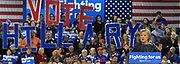 """Hillary Clinton supporters in the background hold up letters that spell out """"Vote Hillary"""" during her speech at the carpenter's training center in Affton."""