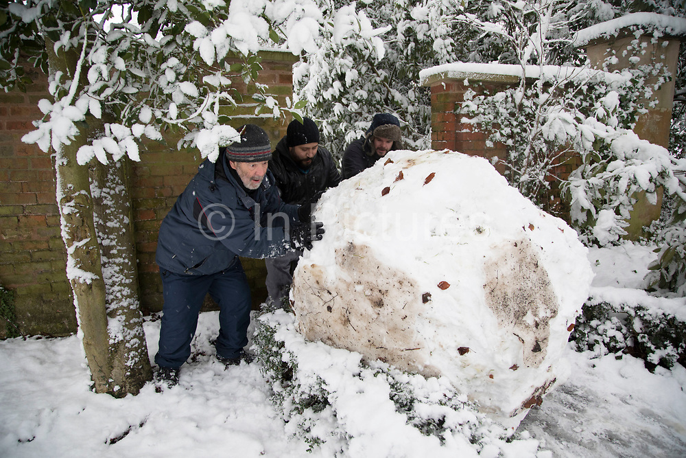 Men having fun rolling a giant snowball to form a snow man in Highbury Park in Moseley after heavy snow fall on Sunday 10th December 2017 in Birmingham, United Kingdom. Deep snow arrived in much of the UK, closing roads and making driving treacherous, while many people simply enjoyed the weather.