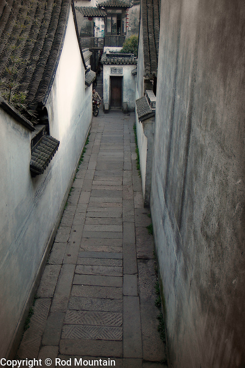 A man drives his moped up the narrow path between buildings in China