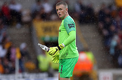 Everton's keeper Jordan Pickford removes a bottle thrown on the pitch during the match at Molineux