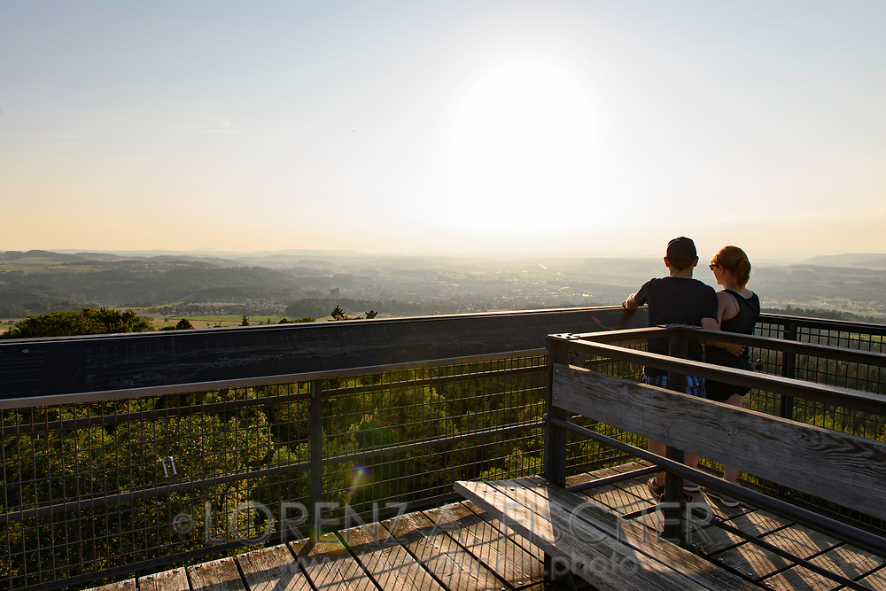 A couple is enjoying the view towards Frauenfeld from the Stäälibuck Tower, a historic steel construction, on a nice and sunny summer evening in July, Thurgau, Switzerland