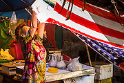 26 APRIL 2013 - BANGKOK, THAILAND:    A woman uses an American flag as the roof for her market stall in Talat Noi. The Talat Noi neighborhood in Bangkok started as a blacksmith's quarter. As cars and buses replaced horse and buggy, the blacksmiths became mechanics and now the area is lined with car mechanics' shops. It is one the last neighborhoods in Bangkok that still has some original shophouses and pre World War II architecture. It is also home to a  Teo Chew Chinese emigrant community.      PHOTO BY JACK KURTZ