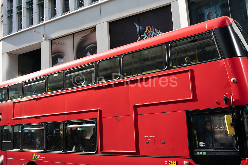 Giant advertising face with full lips and eyes looking down on the people passing below on Fenchurch Street in the City of London, United Kingdom. The atmosphere is one of being watched and of Big Brother watching you.