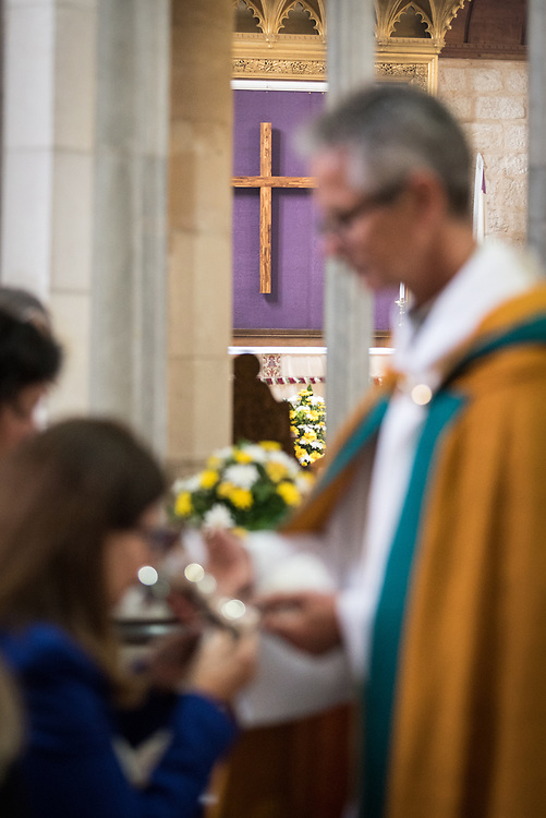 20 April 2019, Jerusalem: Dean Richard Sewell distributes wine during Easter Sunday service at the Cathedral Church of Saint George the Martyr, Jerusalem.