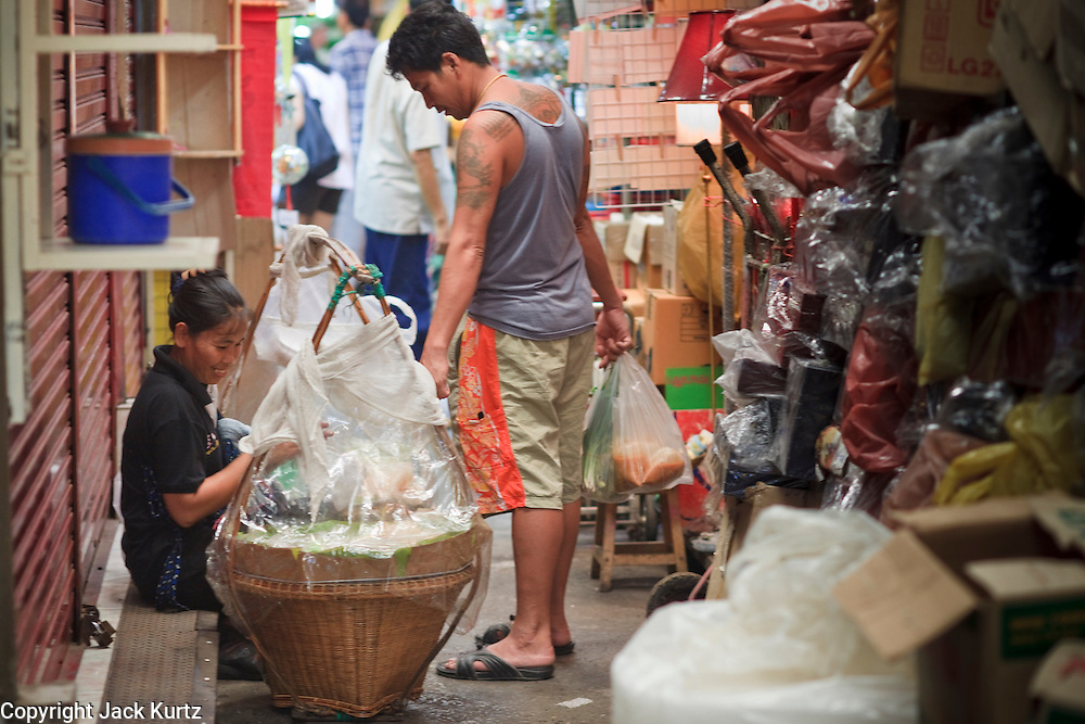 Mar. 8, 2009 -- BANGKOK, THAILAND: A food vendor does business from her bamboo baskets in the Chatuchak Weekend Market. The market covers an area of 35 acres with more than 15,000 shops and stalls. It has over 200,000 visitors each day it's open (Friday - Sunday), and they spend an estimated total of 30 million baht (approx US$750,000). The range of products on sale is extensive, and includes household accessories, handicrafts, religious artifacts, art, antiques, live animals (which unfortunately are frequently caged in cruel conditions), books, music, clothes, food, plants and flowers. Photo by Jack Kurtz / ZUMA Press