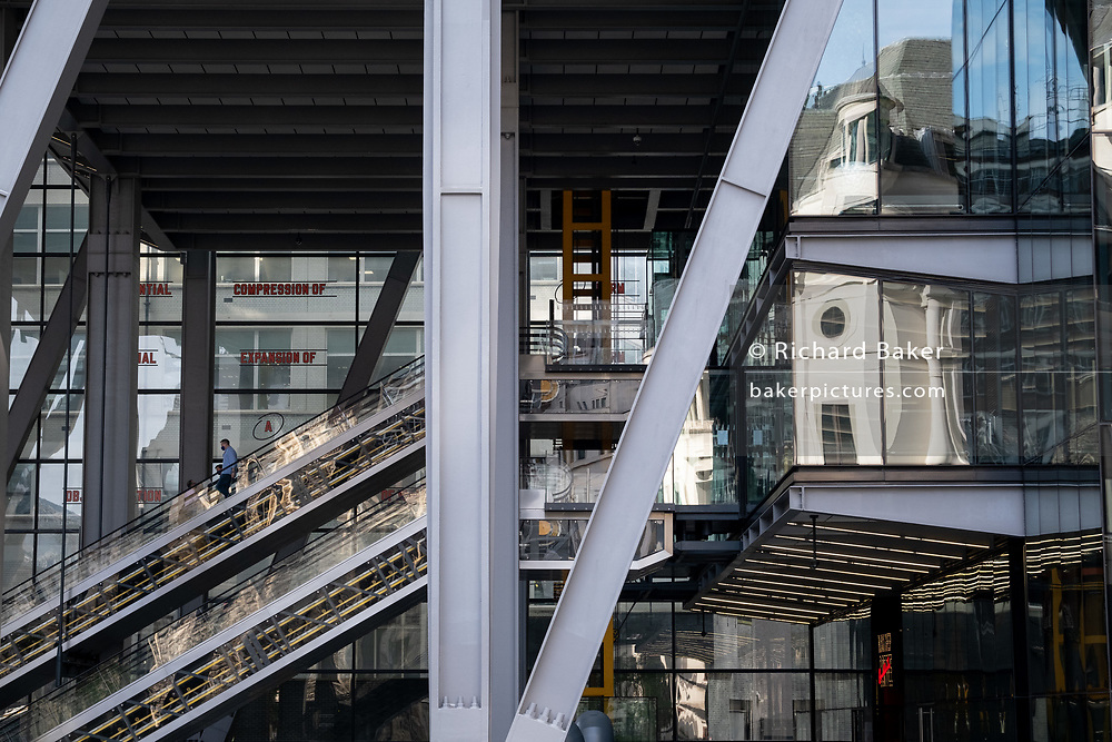 "An office worker descends the escalator at 122 Leadenhall Street, (aka the Leadenhall Building) on Leadenhall Street in the City of London during the Coronavirus pandemic, a time when office workers are still largely still working from home, on 16th September 2020, in London, England. The commercial skyscraper opened in July 2014 and was designed by Rogers Stirk Harbour + Partners and is informally known as ""The Cheesegrater"" because of its distinctive wedge shape."