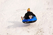 02 JANUARY 2021 - DES MOINES, IOWA: A person rides an inflatable pool toy down the hill below the Iowa Supreme Court. The hill is one of the most popular spots in Des Moines for sledding and winter play. Hundreds of people took advantage the warmer weather and the week's record snow to spend time on the slopes around the Supreme Court and neighboring capitol. The high temperature Saturday was about 25F (-4C).      PHOTO BY JACK KURTZ