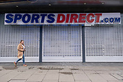 Woman walks past shuttered closed Sports Direct shop along Oxford Street which is largely empty of shoppers as the national coronavirus lockdown three continues on 28th January 2021 in London, United Kingdom. Following the surge in cases over the Winter including a new UK variant of Covid-19, this nationwide lockdown advises all citizens to follow the message to stay at home, protect the NHS and save lives.
