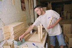 Cabinet maker using nails to construct carcass of bedside cabinet,