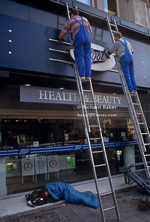 As a sleeping homeless man lies curled up in his sleeping bag on a central London pavement, two window cleaners have carefully placed their ladders at his feet to clean a Boots the chemist sign. Each wearing identical blue working overalls and each wiping the frontage with their left hands, the men are symbolic of the working man versus that of a homeless person without a job, prospects or perhaps a future. The wide gap between hopelessness and the pride of one's achievement is shown here on the sidewalk of modern-day Britain. London is home to some 50,000 homeless people whose place of rest can often be recesses and shop doorways where they seek sanctuary from the cold and street violence. On the opposite end of the wealth and social divides are those who seek work with a positive outlook on life.