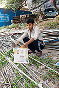 A man reads the morning newspaper atop a tangle of illegal water pipes in the Munika area. New Delhi, India