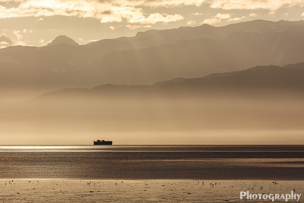 Silvery sunset on shipwreck with mountain ranges silhouetted  in background