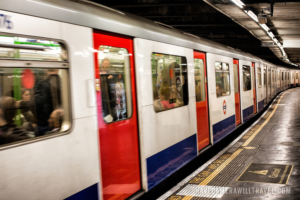 A London Underground train pulling out from the tube stop.