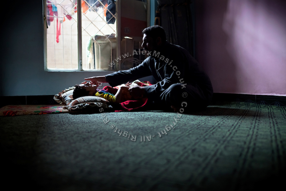 Luay Hadi, 29, is comforting his daughter, Tebah, 7, a child affected by cerebral palsy, in Fallujah, Iraq. Tebah's mother was pregnant during both US-led battles in 2004. The parents and their relatives have no history of birth defects.